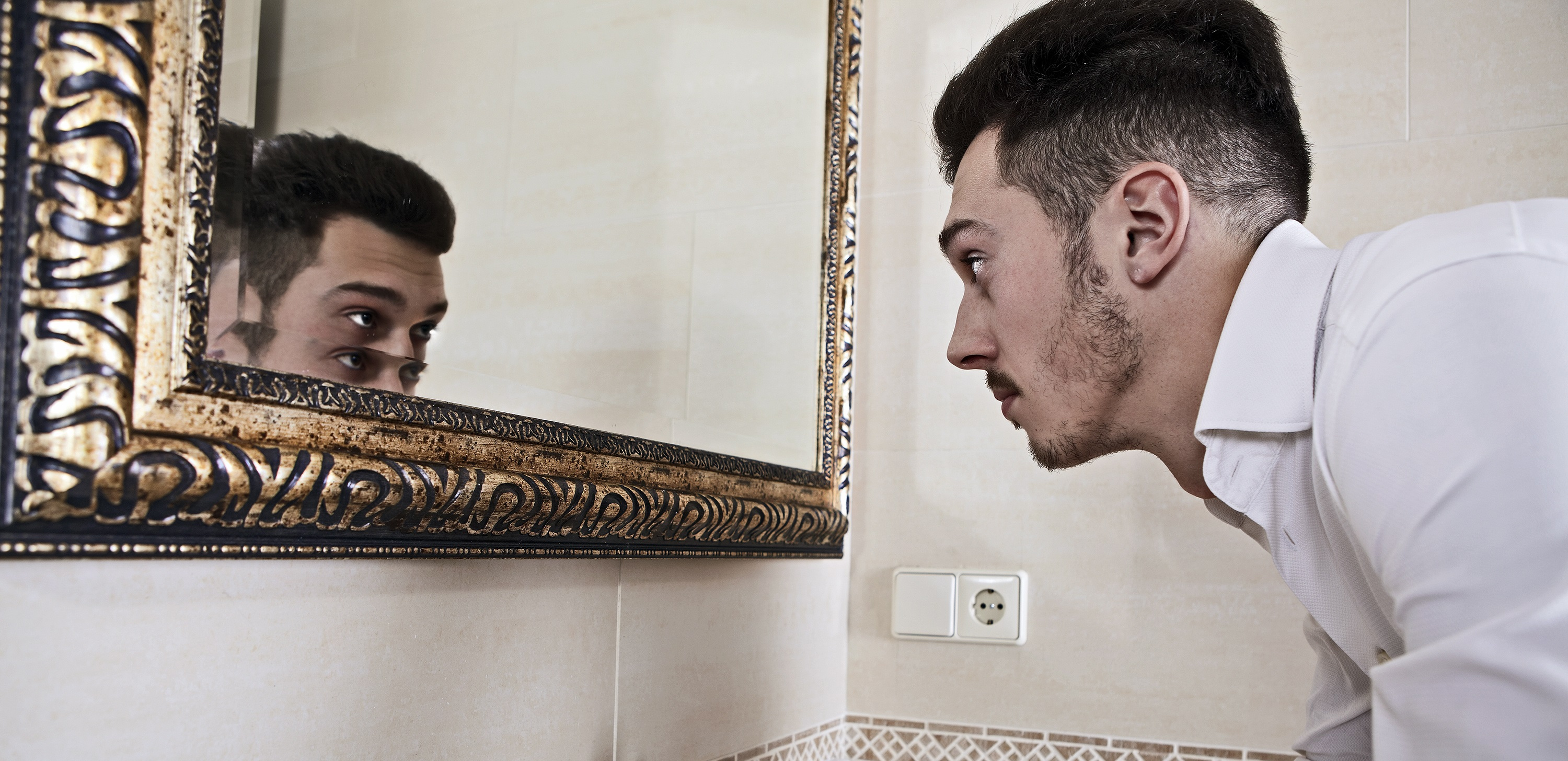Man takes a look at himself in the mirror.